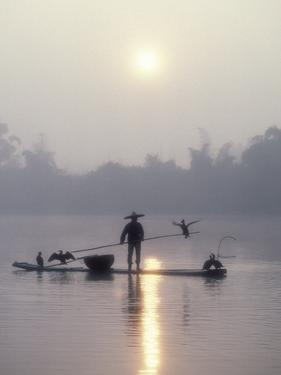 A Fisherman Uses His Cormorants to Catch Fish in the Early Morning by Kenneth Ginn