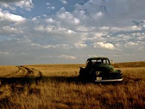 A Landscape of an Old Farm Truck in a Field at Sunset by Kenneth Ginn