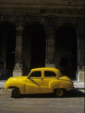 An Old Yellow Car Sits at the Curb in Old Havana by Kenneth Ginn