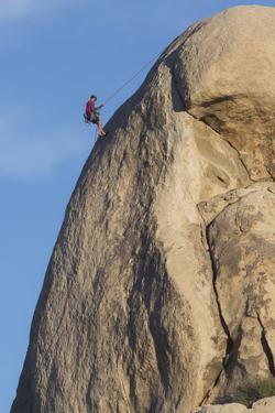 A Climber Repelling Down a Rock Face in Joshua Tree National Park's Hidden Valley by Kent Kobersteen