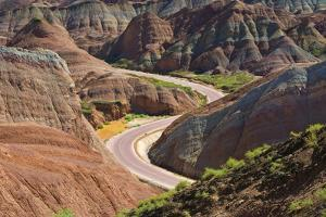 A winding road through the colorful mountains in Zhangye National Geopark. Zhangye, China. by Keren Su