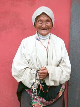 Elderly Tibetan Woman with Red Wall, Tagong, Sichuan, China by Keren Su