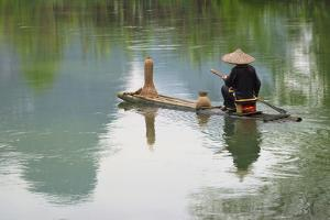 Fisherman on bamboo raft on Mingshi River with karst hills, Mingshi, Guangxi Province, China by Keren Su