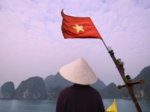 Girl with Conical Hat on a Junk Boat with National Flag and Karst Islands in Halong Bay, Vietnam by Keren Su