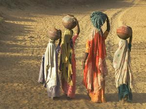 Girls Wearing Sari with Water Jars Walking in the Desert, Pushkar, Rajasthan, India by Keren Su