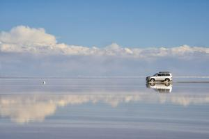 Jeep driving on the reflected surface of the salt flat, Salar de Uyuni, Potosi Department, Bolivia. by Keren Su