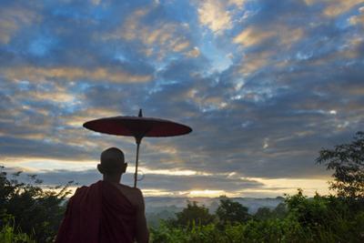 Monk watching ancient temple and pagoda at sunrise, Mrauk-U, Rakhine State, Myanmar