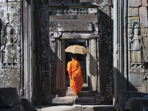 Monk with Buddhist Statues in Banteay Kdei, Cambodia by Keren Su