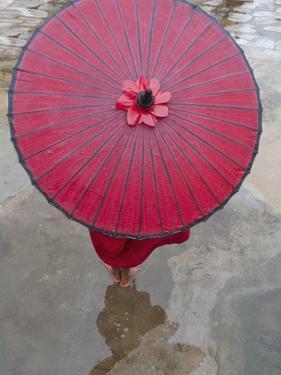 Novice Monk Holding Alms Woks with Red Umbrella, Bagan, Myanmar by Keren Su