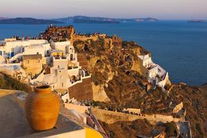 Old fortress and houses on the coast of Aegean Sea. Oia, Santorini Island, Greece. by Keren Su