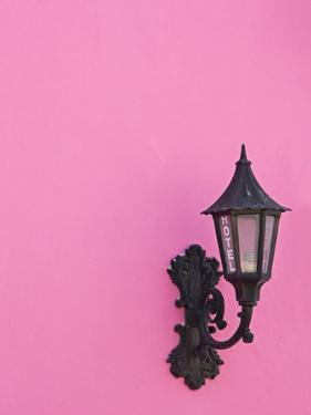 Street lamp on pink wall of Colonial style building by Keren Su
