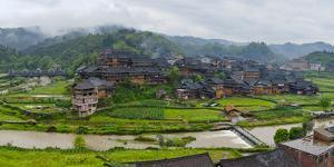 Village with farmland in morning mist, Chengyang, Sanjiang, Guangxi Province, China by Keren Su