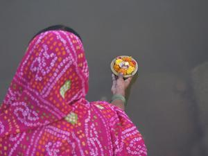 Woman Putting Flower Lamp onto the Ganges River, Varanasi, India by Keren Su