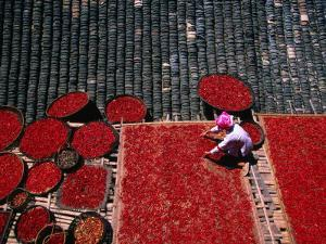 Zhuang Girl Drying Red Peppers on the Roof of Her House, Long Ji, China by Keren Su