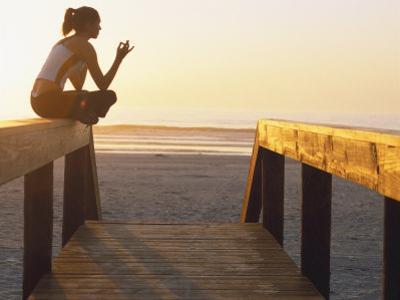 Woman Doing Yoga at Beach During Sunrise