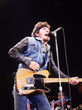 Bruce Springsteen Playing Guitar While Performing on Stage