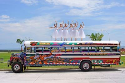 A Ballerina Balancing on Top of a Classical 'Red Devil' Bus