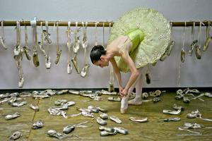 A Ballerina Ties a Pointe Shoe Surrounded by Those She Used in Her Career by Kike Calvo