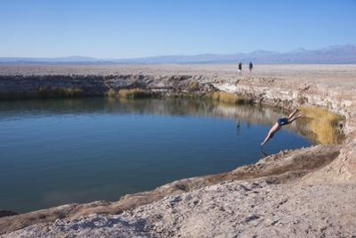 Man Diving into One of the Twin Fresh Lakes (Sala Eyes) in San Pedro De Atacama by Kimberly Walker