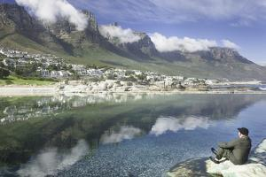 Man Sits on Rock Facing Twelve Apostles Mountain Reflected in Atlantic Ocean, Camp's Bay, Cape Town by Kimberly Walker