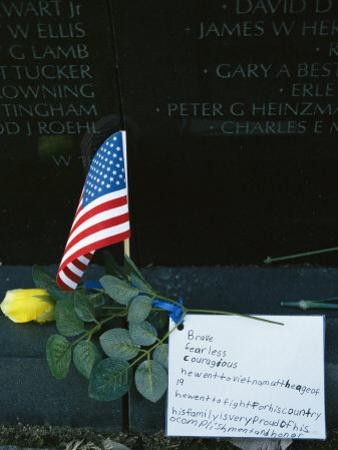 Rose, Flag, and Note of Remembrance Left by a Family at Memorial Wall by Klaus Nigge