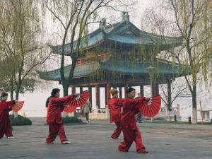 Women Practising Tai Chi in Front of a Pavilion on West Lake, Hangzhou, Zhejiang Province, China by Kober Christian