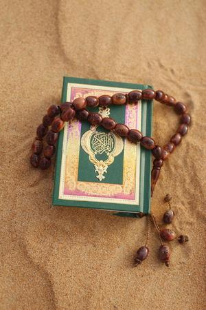 https://imgc.allpostersimages.com/img/posters/koran-and-prayer-beads-in-sand-dubai-united-arab-emirates_u-L-Q1GYJXE0.jpg?artPerspective=n
