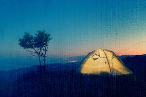 Night Landscape with a Tent in the Mountains. the Light from the Lantern in a Tent. Camping in the by Kotenko