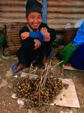 White Hmong Girl with Dried Berries, Looking at Camera, Laos by Kraig Lieb
