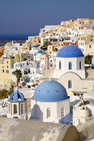 Blue Domes of Greek Orthodox Churches Combine with Colorful Homes in Santorini, Greece