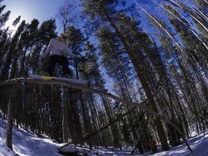 Man Riding Log on Snowboard, Vail, CO by Kurt Olesek