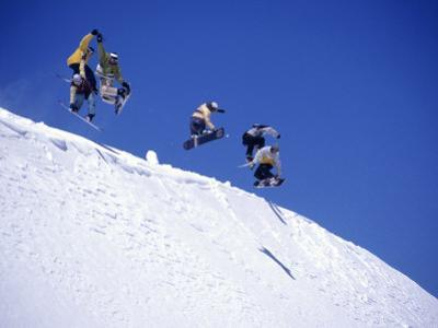 Snowboarders Jumping off Overhang, CO