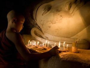 A Novice Monk Lighting Candles at a Massive Buddha Statue in Burma (Myanmar) by Kyle Hammons