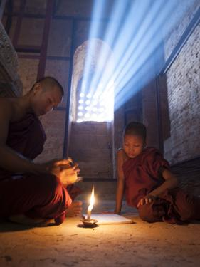 Two Novice Monks Reading Buddhist Texts Inside a Pagoda at Bagan in the Country of Burma (Myanmar) by Kyle Hammons