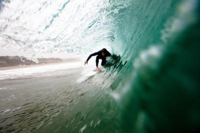 A Male Surfer Pulls into a Barrel While Surfing at Zuma Beach in Malibu, California. by Kyle Sparks