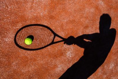 Shadow Of A Tennis Player In Action On A Tennis Court (Conceptual Image With A Tennis Ball