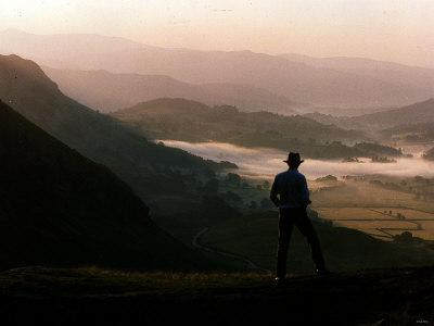 https://imgc.allpostersimages.com/img/posters/lake-district-dawn-rises-in-a-lakeland-pass-watched-by-man-in-hat_u-L-P5F7TR0.jpg?p=0