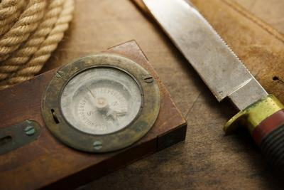 Old Knife, Compass, and Rope on a Old Wooden Desk, Exploration, Survival, and Hunting Concept Image