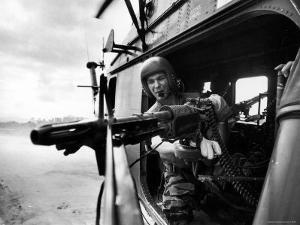 Helicopter Crew Chief James Farley Using M-60 Machine Gun in Landing Zone Near Da Nang by Larry Burrows