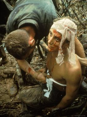 Wounded Marine Being Bandaged in Muddy Jungle During OP Prairie US Military Sweep South of DMZ by Larry Burrows