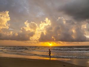 Person walking on beach, South Padre Island. by Larry Ditto