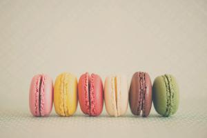 A Rainbow Selection of Sweet French Macarons Sitting in a Row. by Laura Evans