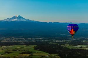 Aerial view of hot air balloon floating over farmland and Mount Rainier, USA by Laura Grier