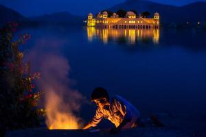 Boy Cooking at Twilight by the Jal Mahal Floating Lake Palace, Jaipur, Rajasthan, India, Asia by Laura Grier