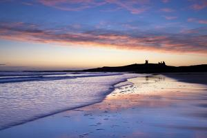 Looking across Embleton Bay at Sunrise Towards the Silhouetted Ruins of Dunstanburgh Castle by Lee Frost