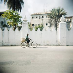 Man on Bicycle with Old Buildings Behind, Stone Town, Zanzibar, Tanzania, East Africa, Africa by Lee Frost