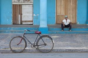 Old Bicycle Propped Up Outside Old Building with Local Man on Steps by Lee Frost