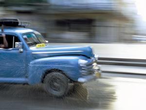 Panned Shot of Old American Car Splashing Through Puddle on Prado, Havana, Cuba, West Indies by Lee Frost