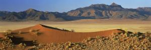 Panoramic View Over Orange Sand Dunes Towards Mountains, Namib Rand Private Game Reserve, Namibia by Lee Frost