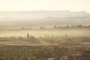 The Town of Tinerhir Soon after Sunrise, Smoke Rising from the Streets and Traditional Houses by Lee Frost